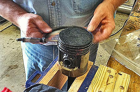 My father measures the outside diameter of a piston.
