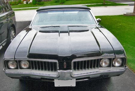 The 1969 Cutlass has vertical grille columns while the 442 has die cast numbers in center of hood.