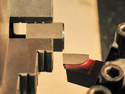 The hex stock segment is held in the lathe's three jaw chuck and an angled cutter is used to cut the relief cut into the Acorn Nut's base per the drawing.