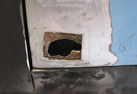 A rust hole in driver's side door was repaired by removing rust until clean metal appeared then welding in new metal.