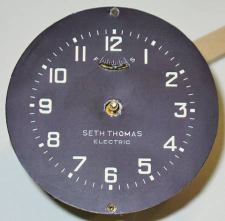 Photo 4 – The completed clock dial face printed out on photo quality paper and applied to the clock's original brass face plate. The background is a uniform black color and the numbers & letters were all set to a light grey and beige (off white) to match the slightly faded numbers & letters of the other face plates in the dash board instrument cluster.