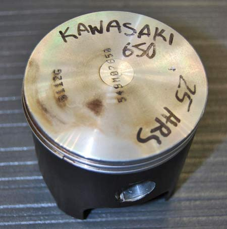 This old piston from a Kawasaki 650 motorcycle has been restored to factory specifications by the application of a black-colored abraded powder coating with a specific hardness and thickness on the piston skirts.