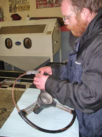 Jesse Gunnell used duct tape to cover repairable sections of the wheel before cleaning the rusty spokes a steel rim core in a media blasting cabinet.