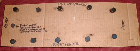 Cardboard panel holds right-hand cylinder head bolts, plus bolt that attaches ATF tube to back of head, with all items labeled for proper positioning.