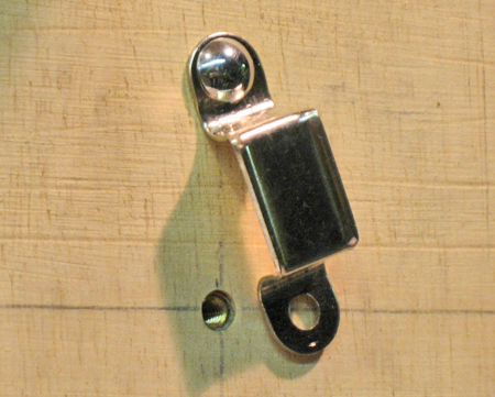 A trunk handle loop is fitted with a threaded rivet. Notice the brass insert is seated just below the surface.