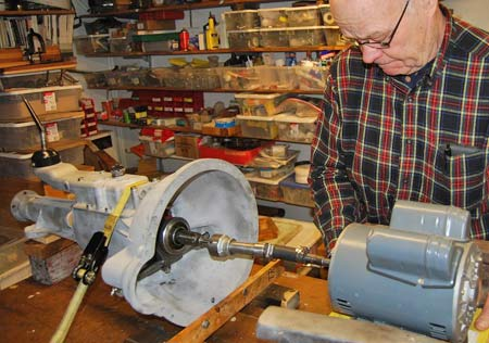 Ken Quade uses this machine of his own invention to test the British car transmissions he rebuilds in Appleton, Wis. Ken uses a yellow tie-down strap to fasten the rebuilt gearbox to his testing apparatus.