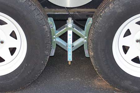 A metal wheel chock is located between the wheels to secure the trailer.