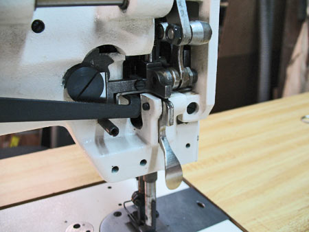 Photo 16: The Presser Bar Lever (accessed from the back of the Presser Foot) raises and lowers both feet, but not the needle. The Presser Foot should be raised when using the bobbin winder or when positioning material under the foot and needle.