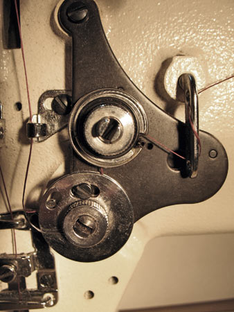 Photo 21: Close up view of the tension adjuster. Thread is routed counterclockwise between the upper disk pair and then down (clockwise) over the hair spring. When the presser foot lever is raised, the tension disks are separated making it easier to route the thread through the adjuster. The serrated thumb nut is the means to adjust the tension.