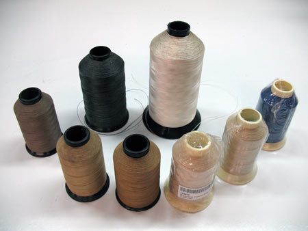Photo 31: Various colors of thread are shown in cones. The large cone of white is a nylon where as the small ones are poly cotton blend. Unique colors are usually offered in smaller cones.