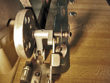 Photo 9: Since the bobbin winder's wheel is snapped into place against the drive belt, when the machine is engaged, it will wind the thread onto the bobbin. Note the little metal finger that will sense when the bobbin gets full.