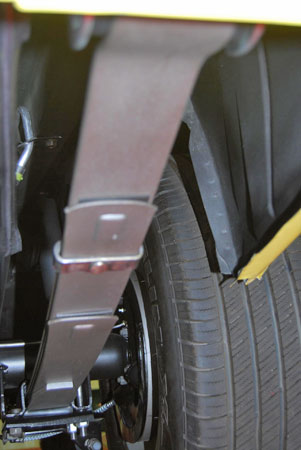 This shows the right-hand rear spring mounting. T-bolts are used on the inside and a U-bolt is used on the outside. The acorn nuts are dimpled to keep them in place. Note staggered shock mounted ahead of axle on right-hand side of car.