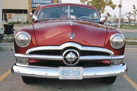 The 1950 Ford has square turn signals and a central bullet.