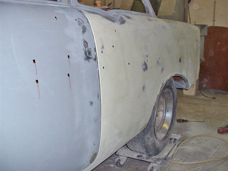 Next up was to install the doors and start the filler work on the sides of the car.  Although the entire quarter panel is covered with filler, the filler is not over 1/16th of an inch thick,. Nice metal work and preparation is a must before apply any body filler.  If done right, plastic filler will last as long as lead filler, if not longer.  You cannot use plastic filler to fill up rust holes or trim holes.  Plastic filler will fail just like lead filler if moisture gets in behind it.
