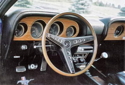 Mach 1 interior has lots of teakwood trim. This car has desirable rimblow steering wheel, four speed and pedal dress up.