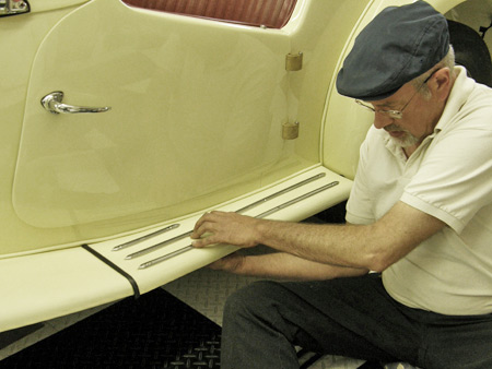 MG T-Series restorer Shane Hanke carefully attaches new chrome running board trim strips to the freshly repainted car.