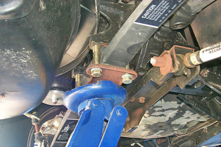 Elevate the car by placing the pad of a floor jack beneath the rear spring securing plate.