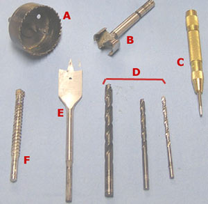 Drill bits: A: hole saw drill; B: Forstner bit; C: Spring-loaded center punch; D: three different-sized metal bits; E: wood bit; F: masonry bit.