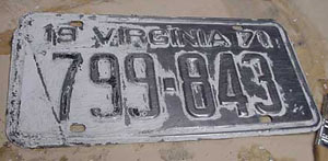 License plate after paint remover was allowed to do its work. This photo shows half of the old paint wiped off.