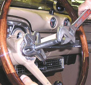 As you slowly tighten the center bolt, it presses on the steering shaft, causing the puller body to lift, pulling the steering wheel with it.