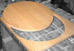 Top (outer) wood circle is cut. Looking carefully, you can see layout lines for center channel and inner ring.