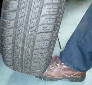 Lifting the tire back onto the car with your foot.