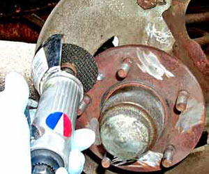 An air-powered cutting wheel is then used to remove the remaining rivet studs. The rivets are no longer required to hold the rotor on, since the lug nuts will secure it.