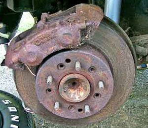 The rear rotors of this car had been replaced earlier, as evidenced by the absence of the factory rotor mounting rivets. Had they been original rotors, the rivets would have to be drilled out for rotor removal. These rotors and calipers have seen better days, so they will be replaced with new units and new brake pads as well.