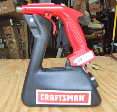 This Craftsman hand-held sandblasting gun from Sears is compact, affordable and very efficient. The large knob below the air connector is the filler cap. The gun holds about 5 lbs. of sand at a time; more than that would make it too heavy and unmanageable.