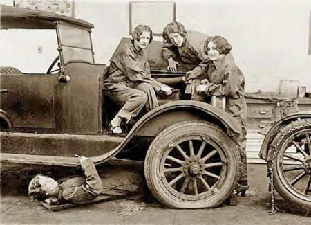 Grace Hurd, Evelyn Harrison and Corinna DiJuliano work on a car engine at Central High school in Washington, D.C., in 1927. Helping them under the car is a young lady named Grace Wagner.