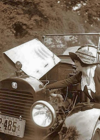 A well-dressed woman tinkers under the hood of a car with 1920 New York dealer plates. Dealers today say they'd like to hire more woman service technicians, but can't find enough of them.