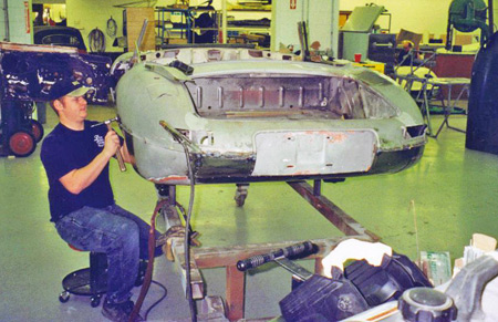 A worker at L'Cars uses an old fashioned hammer and dolly to reshape some Jaguar sheet metal