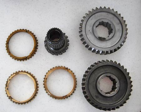 The top row shows a synchro ring on left and a cleaned up reverse gear on the right. Bottom left is an improved purged brass synchro ring. Next to it is a regular and less expensive brass synchronizer ring. On the right, a reverse gear before being cleaned up.