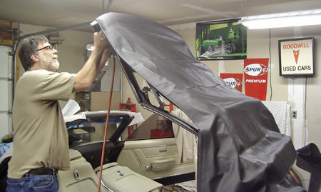 An installer uses an air stapler and stainless steel staples to attach the front of the new convertible  top to the header bar.