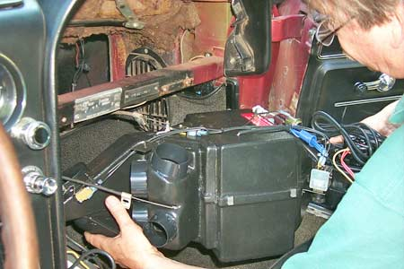 The Vintage Air unit contains the A/C evaporator as well as the heater core and fan. It sandwiches between the firewall and the dashboard cross-member.