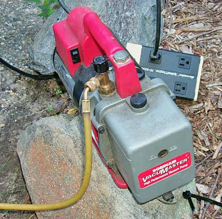 A suction pump is used to evacuate the system for 35-45 minutes at a temperature of at least 85 degrees. On a cooler day the components can be heated with a hair dryer or by running the engine with the heater on before evacuating.