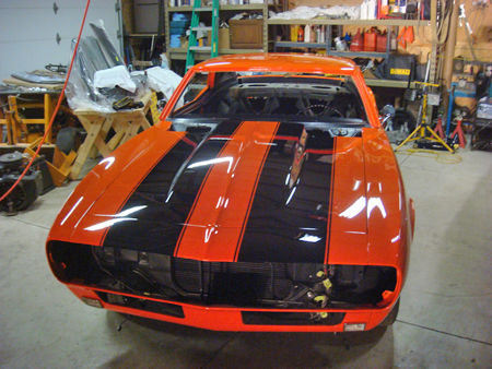 Twin black racing stripes also set off the orange paint on the cars hood the